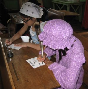 Children at desks in the Museum Schoolhouse